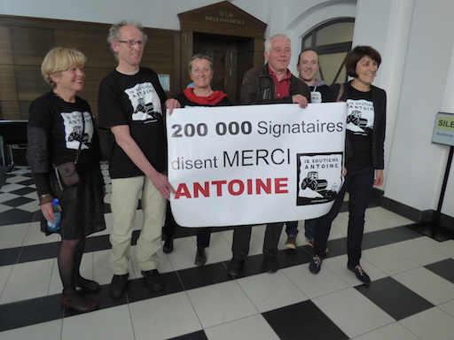 "Members of the support commitee behind a sign: ""200,000 signatories say THANKS to Antoine"""