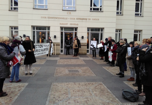 People holding signs and banners welcome Antoine in front of the court's entrance