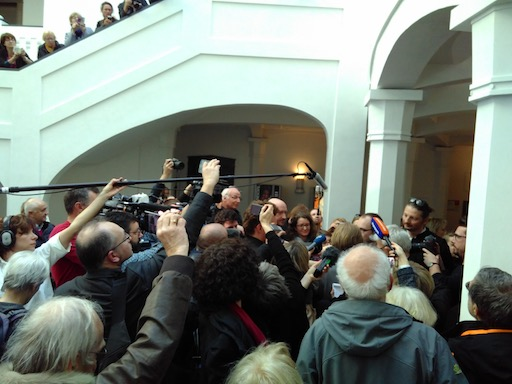 Numerous journalists surrounding Antoine and his lawyers, with boom mikes and cameras