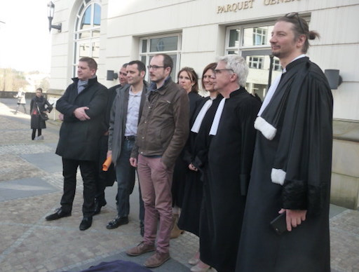 Group photo of the three defendants and their lawyers, in front of the courthouse