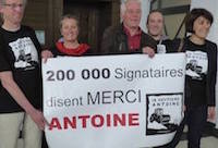 Members of the support committee, standing behind a banner celebrating the first 200,000 petition signatories